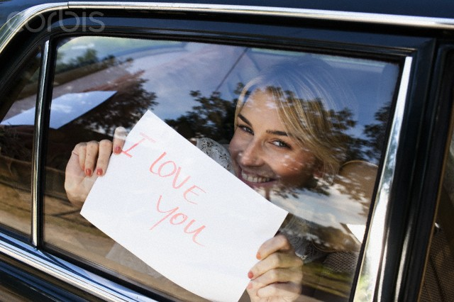 "Young woman holding a sign saying ""I Love You"" up to a car window --- Image by © Oliver Rossi/Corbis"